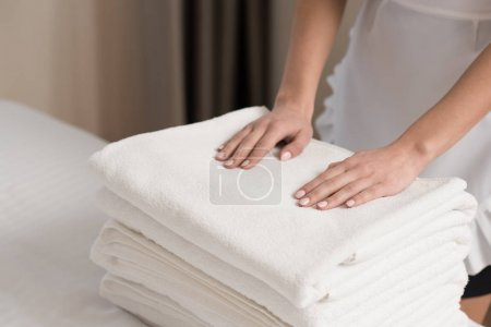 young beautiful maid in uniform with stack of clean towels