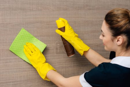 close-up shot of young maid in uniform wiping wood wall with rag and aerosol furniture cleaner