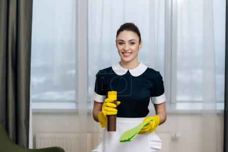 Photo for Young beautiful maid in uniform with rag and aerosol furniture cleaner - Royalty Free Image