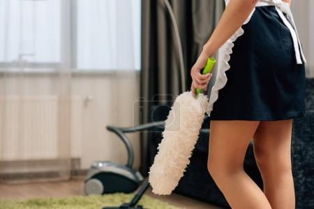 cropped shot of maid in uniform holding duster at hotel suite