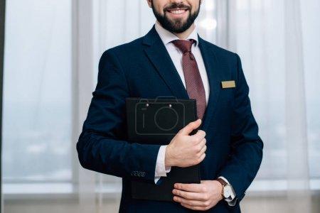 Photo pour Plan recadré de l'administrateur de l'hôtel souriant avec presse-papiers - image libre de droit