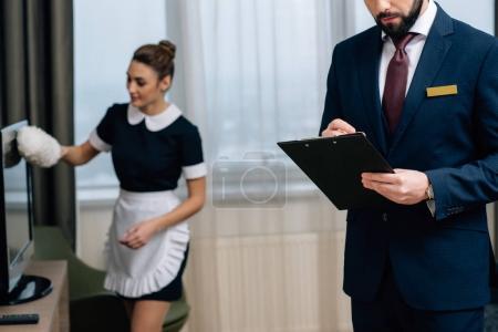 Photo pour Administrateur de l'hôtel écrivant dans le presse-papiers tandis que la femme de ménage nettoyage suite avec plumeau - image libre de droit