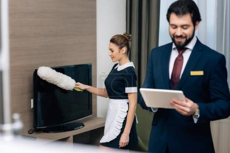 hotel administrator using tablet at suite while maid working with duster