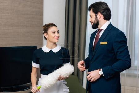 young happy hotel service staff talking at suite