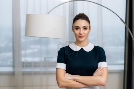 Photo pour Jeune jolie femme de ménage en uniforme avec les bras croisés à la suite de l'hôtel - image libre de droit