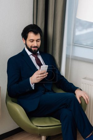 handsome businessman using smartphone while sitting in armchair