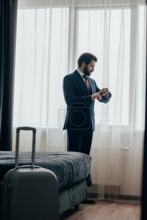 handsome businessman in hotel suite looking at watch while standing near window