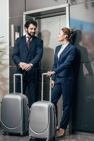 happy young business people with luggage waiting for elevator together