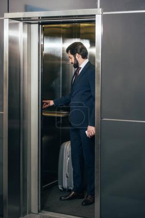 businessman with luggage pressing button inside elevator