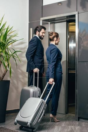business people with luggage entering elevator together