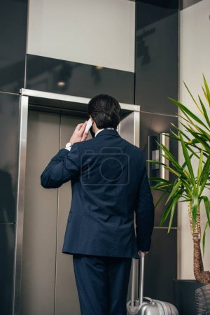 businessman with luggage talking by phone while waiting for elevator at hotel
