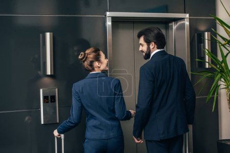 rear view of business people with luggage waiting for elevator together