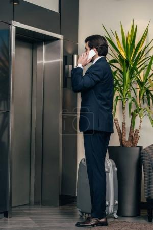stylish businessman with luggage talking by phone while waiting for elevator at hotel