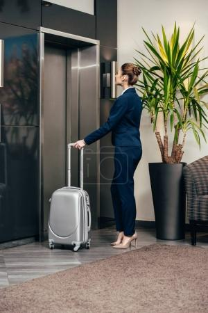 young attractive businesswoman waiting for elevator at hotel with luggage