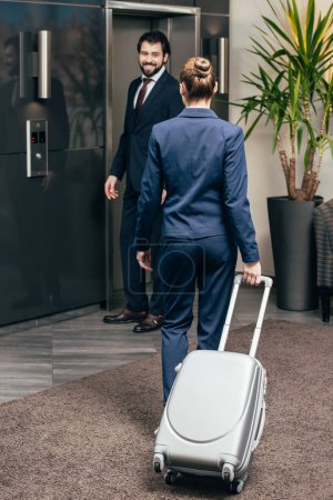 business people with luggage going on elevator together