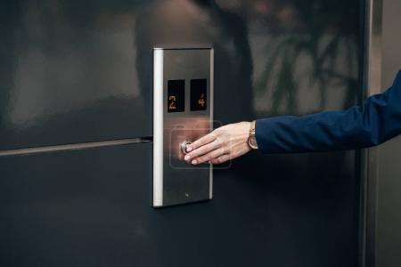 cropped shot of businesswoman pressing button of elevator