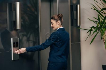 young attractive businesswoman pressing button of elevator