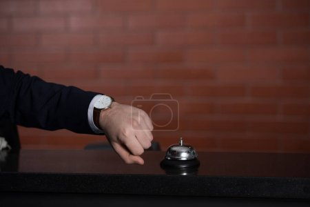 Photo for Cropped shot of businessman looking at watch while waiting for service at hotel reception desk - Royalty Free Image