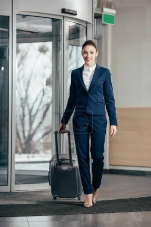 young attractive businesswoman going out of hotel with luggage