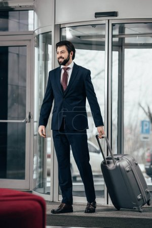 handsome businessman with luggage going out of hotel