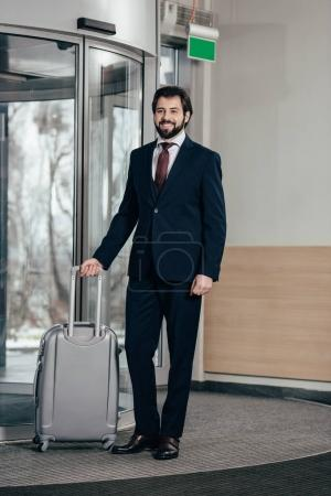smiling handsome businessman with luggage going out of hotel