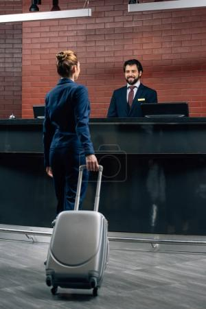 businesswoman with luggage going at hotel reception counter