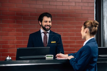 hotel receptionist talking to customer while she signing contract at counter