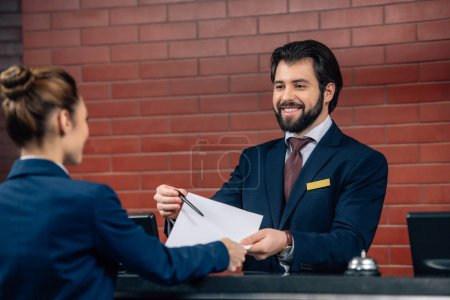 hotel receptionist showing contract customer at counter