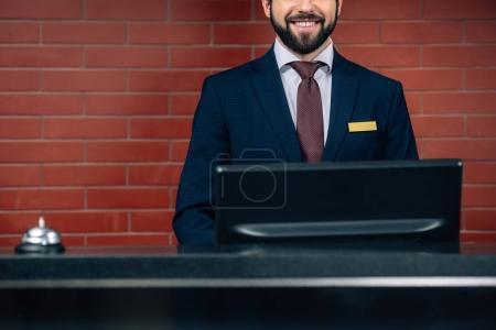Photo pour Plan recadré de la réceptionniste souriante barbu de l'hôtel sur le lieu de travail - image libre de droit
