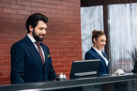 hotel receptionists working with computers together at counter