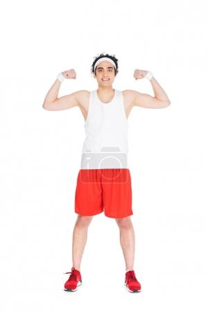 Young thin man in sportswear showing muscles isolated on white