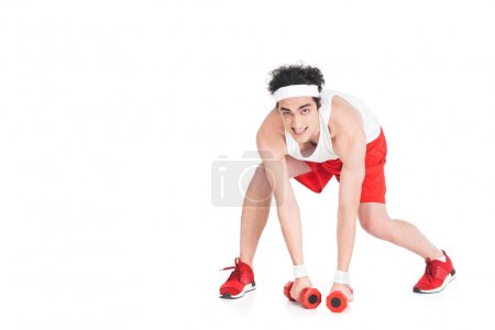 Young skinny man in jogger shoes and shorts with dumbbells isolated on white