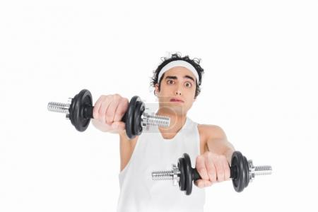 Portrait of skinny young man in sportswear holding dumbbells isolated on white