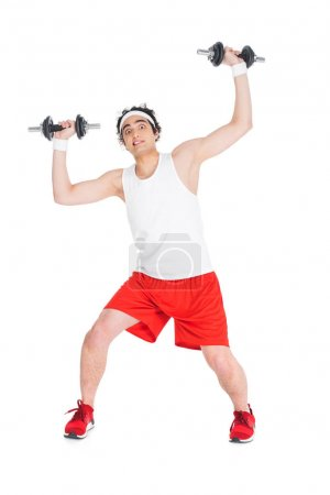 Young skinny man in sportswear holding dumbbells isolated on white
