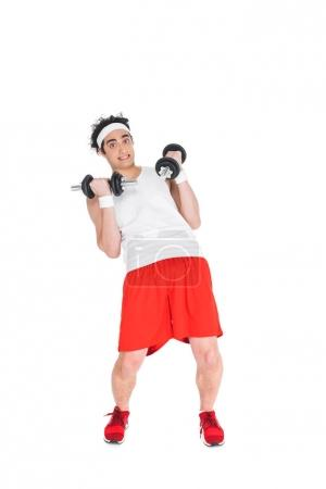 Thin man in headband exercising with dumbbells isolated on white