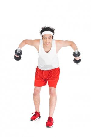 Young thin man in sportswear exercising with dumbbells isolated on white