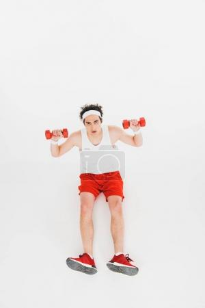 Skinny sportsman sitting on floor with dumbbells isolated on white
