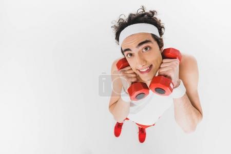 Photo pour Vue grand angle du sportif maigre tenant des haltères près du visage isolé sur blanc - image libre de droit