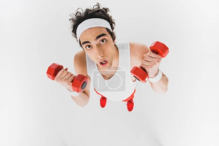 High angle view of thin sportsman with dumbbells isolated on white
