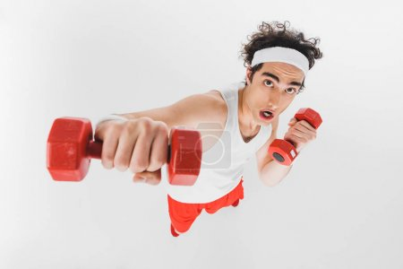 High angle view of young thin sportsman fist with dumbbell isolated on white