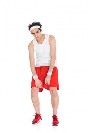 Young thin sportsman in shorts and jogging shoes isolated on white