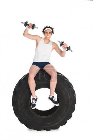 Young thin sportsman with dumbbells sitting on tire of wheel isolated on white