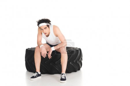 Tired thin sporstman sitting on tire of wheel isolated on white