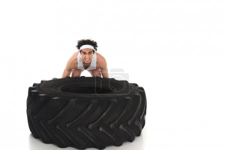 Photo for Young skinny sportsman raising tire of wheel isolated on white - Royalty Free Image