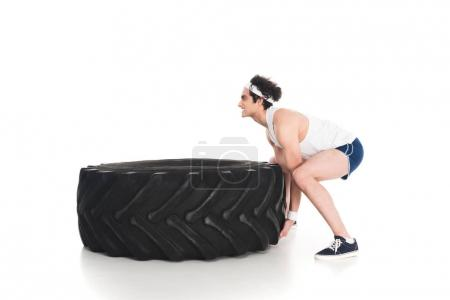 Photo for Side view of skinny sportsman raising big tire of wheel isolated on white - Royalty Free Image