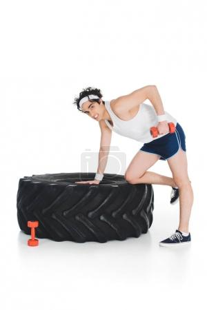Sportsman thin exercising with dumbbell near tire of wheel isolated on white