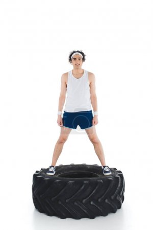 Young thin sportsman standing on tire of wheel isolated on white
