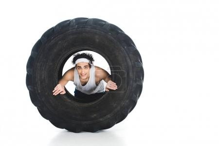 Thin sportsman with headband inside tire of wheel isolated on white