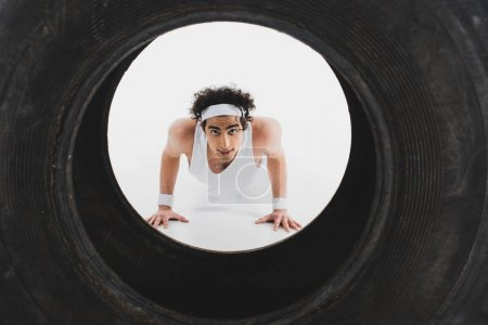 Thin sportsman doing push ups with tire on foreground