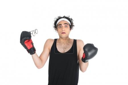 Shocked thin young boxer taking off eyeglasses isolated on white